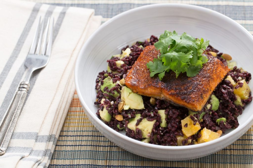 Black rice cooked in a cauldron with salmon