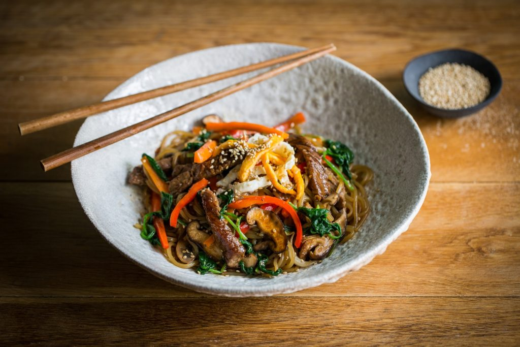 Noodles with guinea fowl and vegetables in a wok
