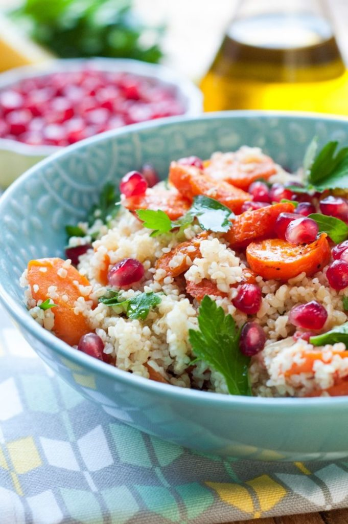 Tasty and exotic warm salad with fruits, bulgur and tortilla
